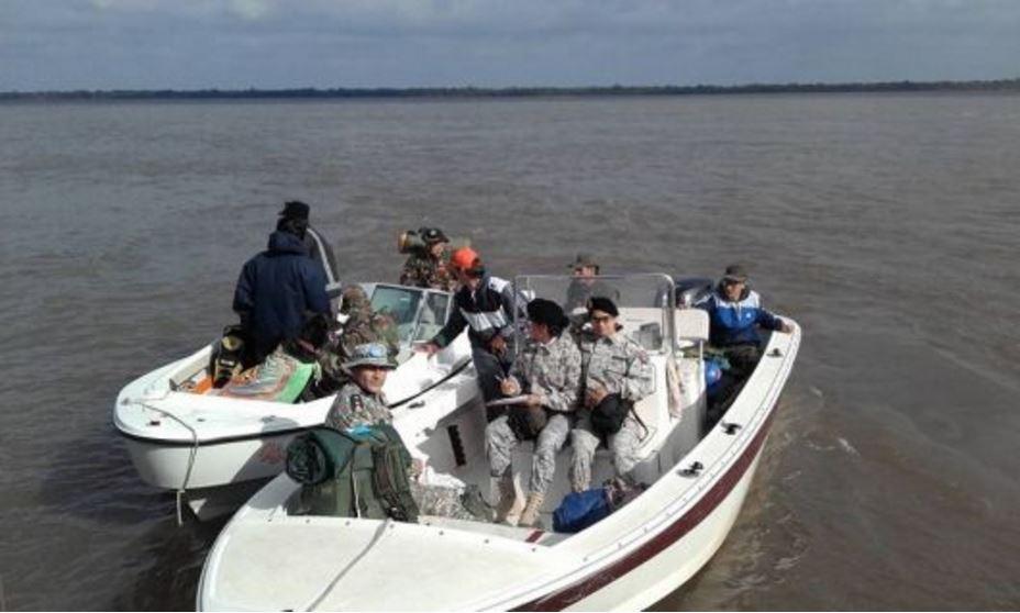 botes buscando cuerpos en el río