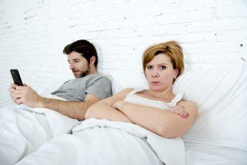 pareja en la cama el con celular