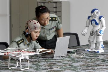 A student (L) and an instructor look at a computer as they demonstrate using a headset to control robots with her mind, at the People's Liberation Army Information Engineering University, in Zhengzhou, Henan province, China, August 7, 2015. The robots can be controlled through the headset to go different directions, turn their heads and pick up objects, local media reported. (Photo by Reuters/Stringer)